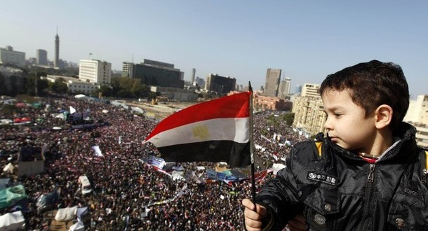 A boy holds an Egyptian flag during a protest marking the first anniversary of Egypt's uprising at Tahrir square during in Cairo
