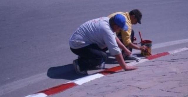 عمال يصبغون جنبات الرصيف