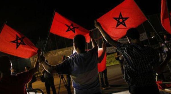 Moroccans from a human rights association hold Moroccan flags during a protest in the border area which separates Spain from Morocco in Nador