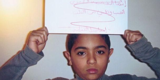 """ابن حسن العمراني يحمل لافتة كتب عليها:""""حذار من تصفية أبي"""""""